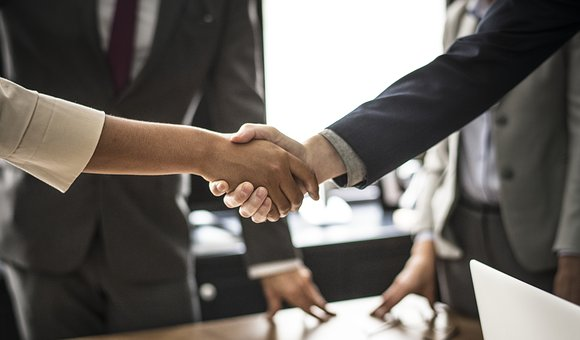 people shaking hands when closing an agreement