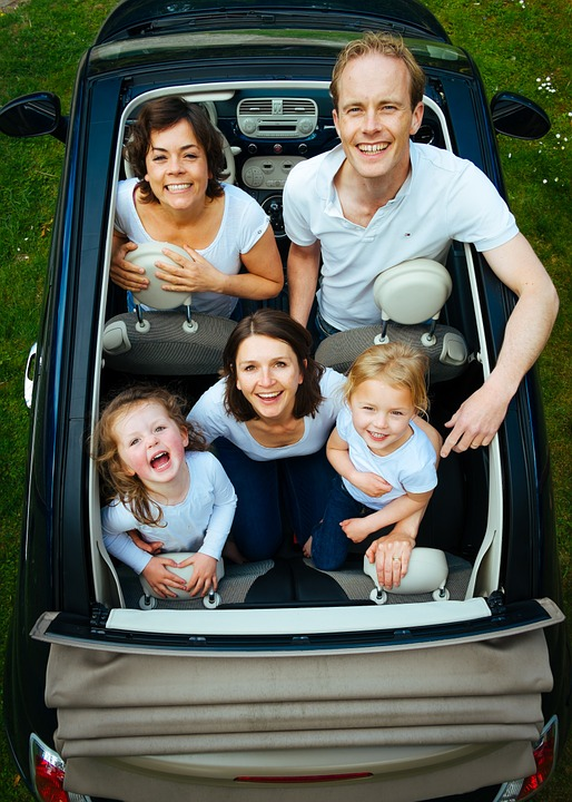 a mother and father with three children in a car with no roof