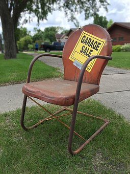 a garage sale sign on a red chair in a backyard