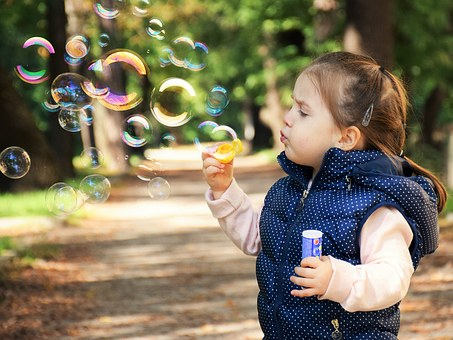 a girl blowing balloons in the park