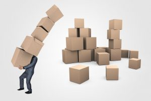 Man struggling to carry a lot of cardboard boxes