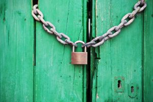green door closed with a lock and a chain