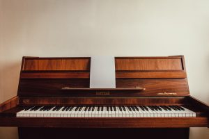 brown upright piano with sheet music