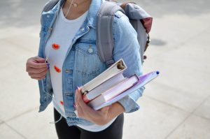 person holding books and carrying a backpack